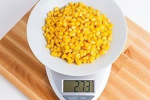 274 grams of canned yellow corn on a scale