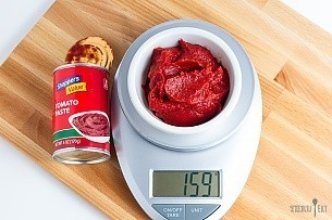 159 grams of tomato paste on a scale